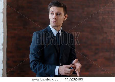 Businessman wearing wrist watch standing near office window looking away