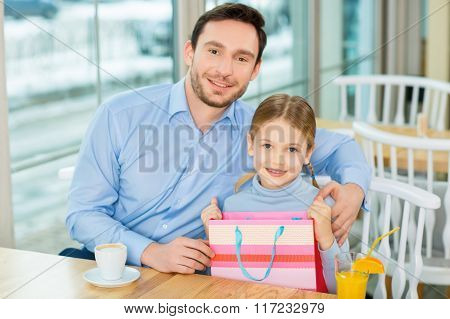 Joyful father sitting and hugging dear kid at the cafeteria.