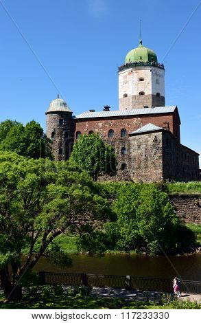 VYBORG, LENINGRAD OBLAST, RUSSIA - JUNE 6, 2015: People on the embankment and on the tower of St. Olav of Vyborg Castle. The castle was founded in 1293