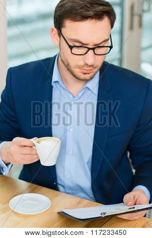 Young good-looking man thoroughly exploring papers