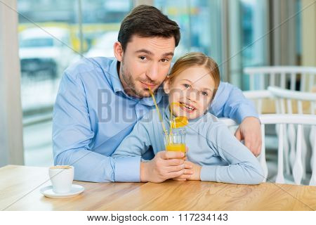 Lovely daughter sharing her orange juice with father
