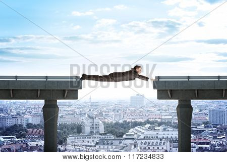 Businessman linking broken bridge