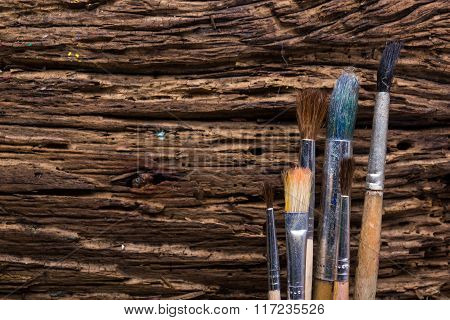 Row of artist paintbrushes close up on old natural rustic grunge