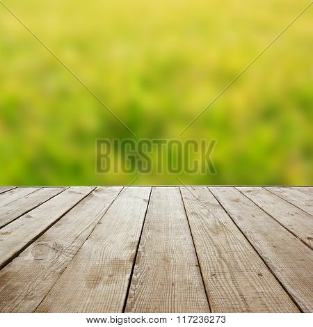 Wooden perspective floor with planks on blurred natural summer b