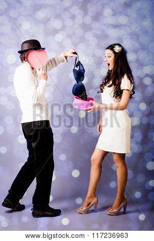 Romantic young man holding present for girl, elegant bra