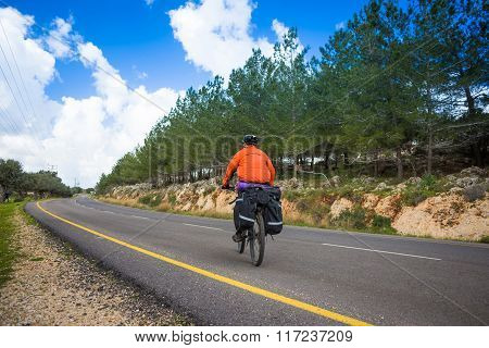 A male cyclist riding a bike along a road. Sunny day
