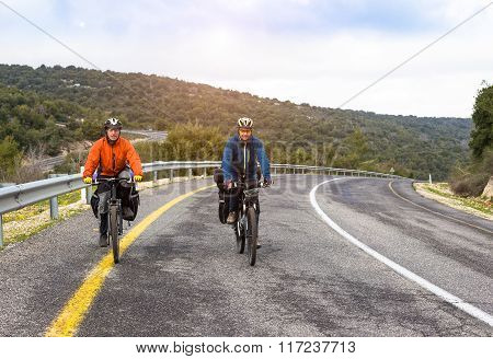 Male cyclists riding bike along road. Sunny day