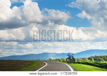 Biking Road On Hill With Big Clouds On The Sky