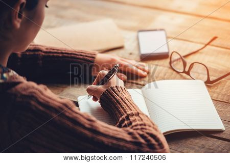 Making notes. Close-up image of woman writing in notebook with copy space while sitting at the rough wooden table