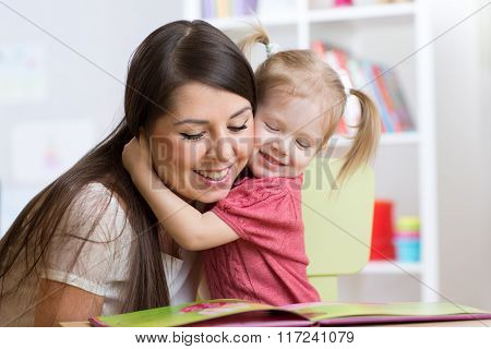 mother  embracing and reading  a book to kid at home