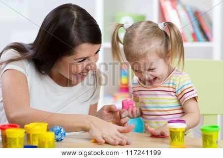 child with mom make by hands playing with color dough