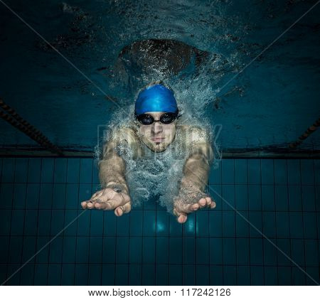 Male swimmer at the swimming pool. Underwater photo.