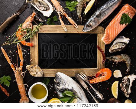 Fresh seafood on black stone with empty sheet, close-up.