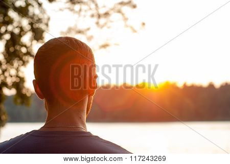 Man looks at the sunset. Sunset on the lake. Flecks of sunlight. In the countryside