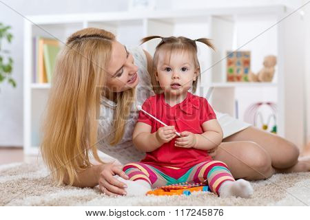 Mother is showing child how to play xylophone toy