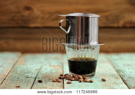 Vietnamese Black Coffee Brewed In French Drip Filter On Turquoise Wooden Table