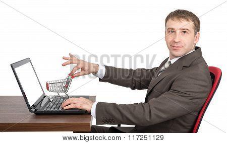 Businessman giving shopping cart to laptop