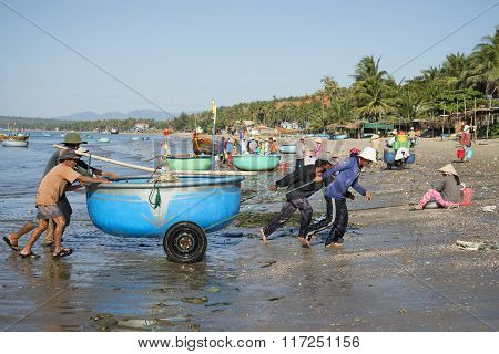 Fishermen pull a plastic boat from the sea. The fishing harbor of Mui Ne, Vietnam