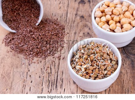 Bowls Of Various Legumes And Seeds. Flaxseed, Peanuts, Chickpeas.