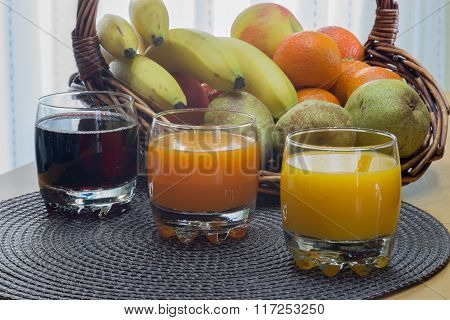 Multi fruit citrus juice from oranges, lemons, bananas, grapes in a glass with fruit basket