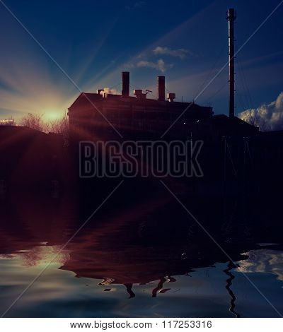 Silhouette of power plant on the sea coast with reflection in water