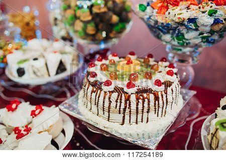 cake decorated cherries with butter cream and poured chocolate