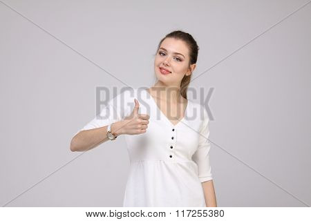 Thumb up. Woman on gray background. Female model.