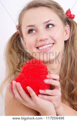 Close-up Portrait Of A Smiling Teenage Girl With Red Heart