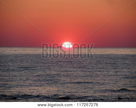 Warm Sea Sunset With Cargo Ship In The Background