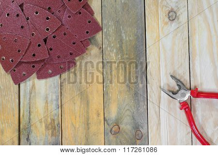 Triangle Sand Papers On Wooden Boards With Pliers Diagonally