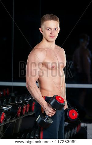 Handsome power athletic man with dumbbell confidently looking forward. Strong bodybuilder six pack,