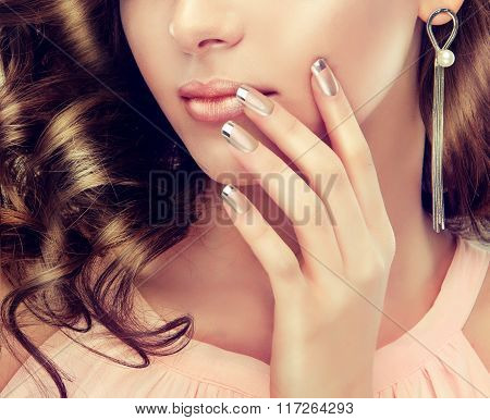 Beautiful girl showing silver French manicure nails . makeup and cosmetics