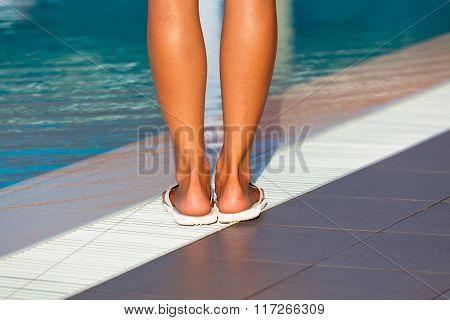 Woman Legs Standing On The Edge Of Swimming Pool