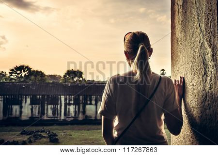 young woman standing at the edge of building and looking at view during sunset through ancient windo