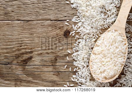 White Rice In Spoon On Wooden Table Top View
