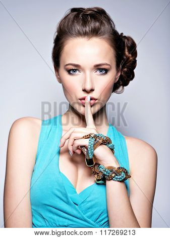 Young beautiful woman with jewelry. Girl Fashion model. Silence,  quiet sign