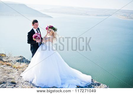 Charming Bride In A Wreath And Elegant Groom On Landscapes Of Mountains, Water And Blue Sky At Sunny