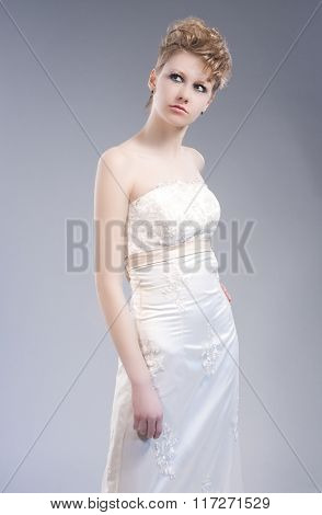 Fashion Concepts. Young Sexy Blond Woman In Nicely Tailored Wedding Dress Posing Against Gray Backgr