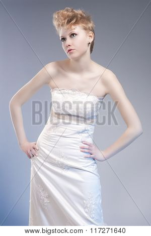 Fashion Concepts. Tall Young And Sexy Blond Woman In Tailored Wedding Dress Posing Against Gray Back