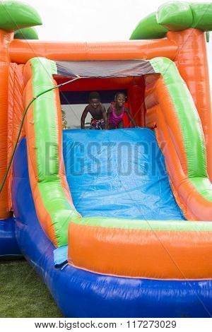 Happy smiling children playing on an inflatable slide bounce house