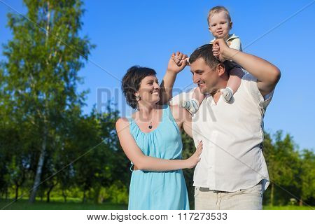 Human Relationships Concepts. Young Caucasian Family Of Three People Having Good Time Together Outdo