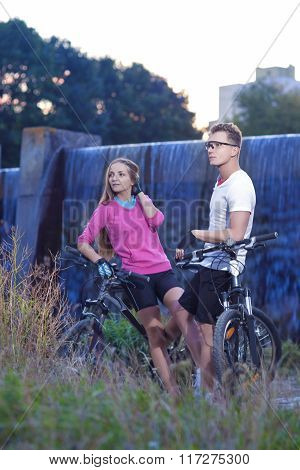 Two Caucasian Lovers With Mtb Bicycles Outdoors. Posing Against Waterfall.