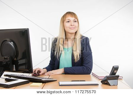 Beautiful Girl Secretary Working At A Computer Looked At Visitor