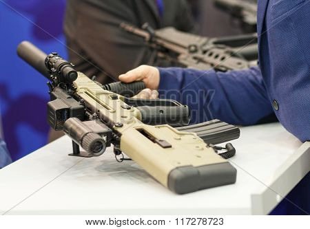 Automatic Rifle In His Hand. Exhibition And Sale Of Weapons