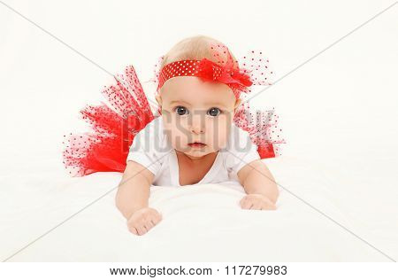 Beautiful Little Baby Girl Lying In Red Skirt On Bed