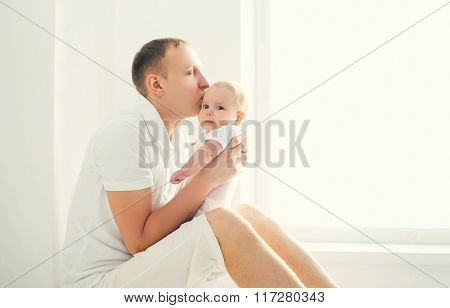 Happy Young Father Kissing Baby At Home In White Room Near Window