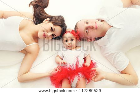 Portrait Happy Family Together Mother, Father And Baby Lying On Bed At Home, Top View