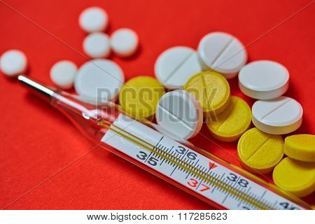 Mercury thermometer and medical pills on background