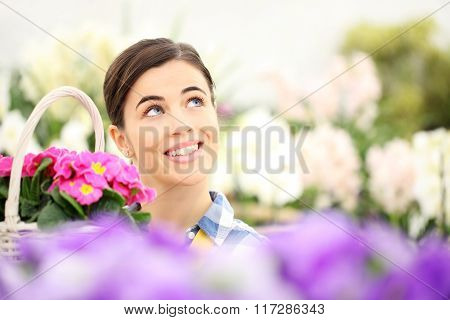 Springtime Woman Smiling In Garden And Looking Up With White Wicker Basket Flowers Of Purple Primros