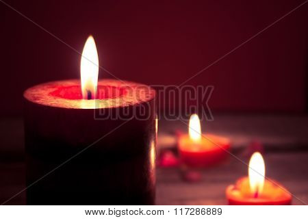 Red Burning Candles On Rustic Wooden Table. Valentine's Day And Mother's Day Background. Toned Image